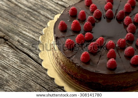 Overhead view of tasty raw chocolate cake decorated with raspberries inviting you to indulge yourself into sweet temptation, placed on a golden plate and textured rustic wooden desk. - stock photo