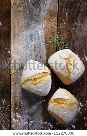 Overhead view of three freshly baked bread rolls lightly dusted with flour on a wooden table top - stock photo