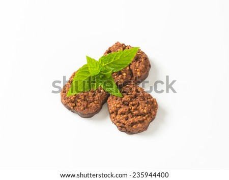overhead view of three wholegrain chocolate chip cookies with fresh mint - stock photo