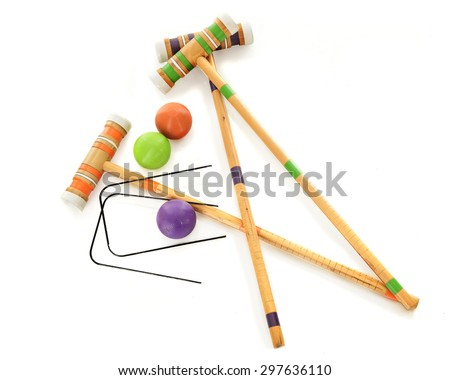 Overhead view of three wooden croquet mallets with matching balls and two black wickets.  On a white background. - stock photo
