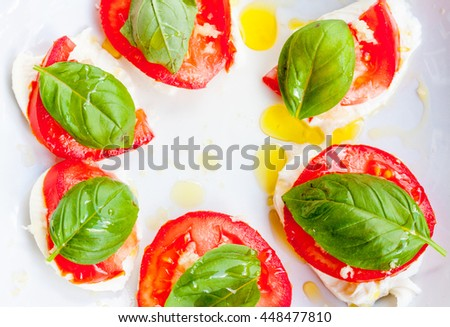 Overhead view of tomato, mozzarella and basil salad drizzled with olive oil on a white plate