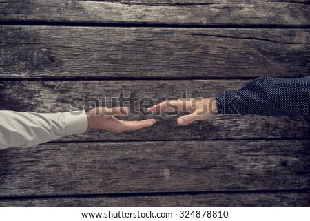 Overhead view of two businessman about to shake hands in congratulation, agreement or greeting over a rustic textured wooden surface, with a retro effect. - stock photo