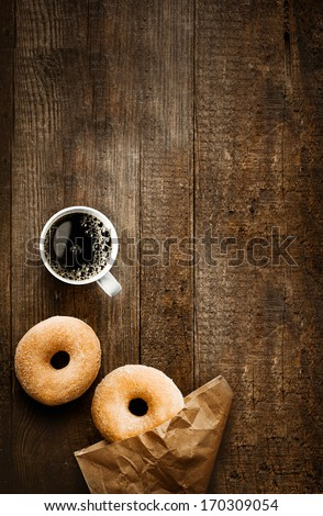 Overhead view of two tempting fresh sugared doughnuts with their brown paper wrapping and a cup of strong black filter or espresso coffee on a rustic wood table - stock photo