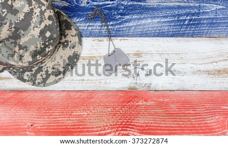Overhead view of United States of America national colors of red, white, blue on aging boards with military cap and identification tags. Patriotic concept.  - stock photo
