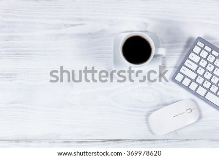 Overhead view of white desktop with partial keyboard, black coffee and computer mouse.