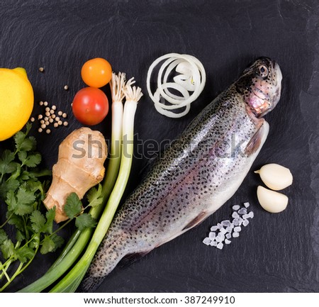 Overhead view of whole fish with various herbs, vegetables, and spices on black natural state. Healthy food concept.  - stock photo
