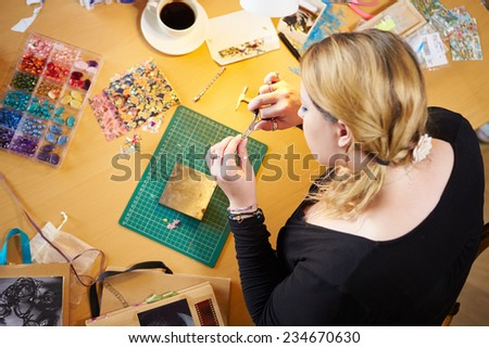 Overhead View Of Woman Making Jewelry At Home - stock photo