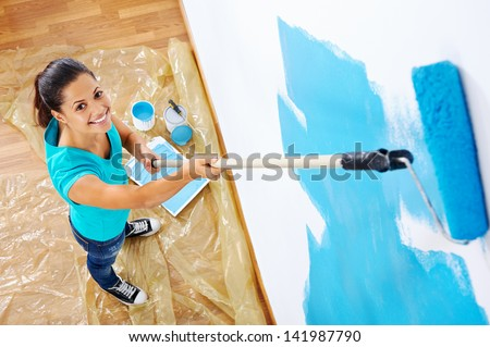 overhead view of woman painting new apartment standing on wooden floor - stock photo