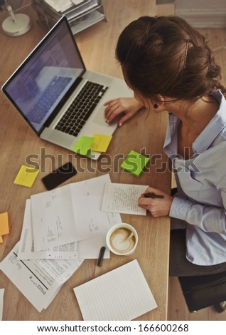 Overhead view of young brunette using laptop while at work. Businesswoman working at her desk. - stock photo