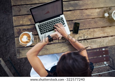 Overhead view of young woman checking time on her smartwatch while working on her laptop at a cafe. Top view shot of female sitting at a table with a cup of coffee, laptop and mobile phone. - stock photo
