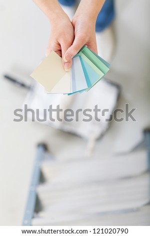 overhead view of young woman choosing paint color for the new home - stock photo