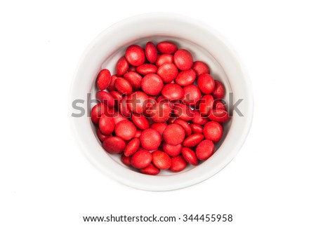 Overhead view on bowl of red color chocolate coated candy in white background - stock photo