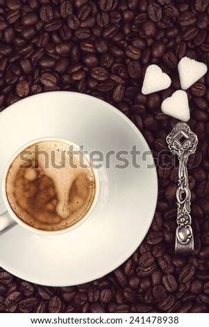 overhead view on cup of espresso coffee  and roasted beans with sugar and silver spoon - stock photo