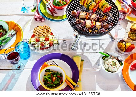 Overhead Well Laid summer table with colorful dish and plates and brazier on white background with vegan bbq skewers - stock photo