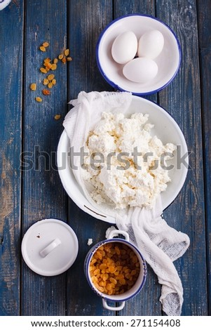 Overhead with homemade ricotta cheese, egg, raisins over kitchen rustic table. See series. - stock photo