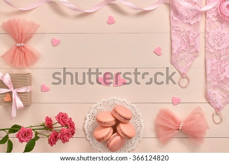 Overhead woman essentials fashion wedding accessories set. Lace gloves, macarons, gift box, hearts love and roses. Creative bride set, vanilla wooden background. Romantic modern, still life. Top view - stock photo