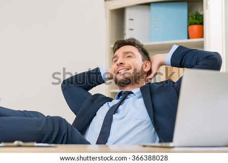 Overjoyed office worker sitting at the table
