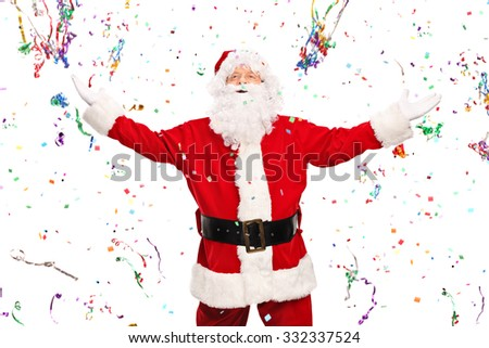 Overjoyed Santa Claus standing in the middle of a bunch of flying confetti streamers isolated on white background - stock photo