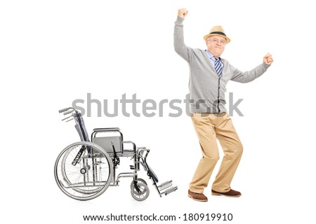 Overjoyed senior adult standing up from a wheelchair isolated on white background - stock photo
