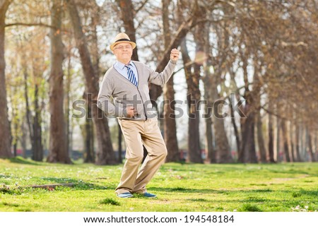 Overjoyed senior playing air guitar in park  - stock photo