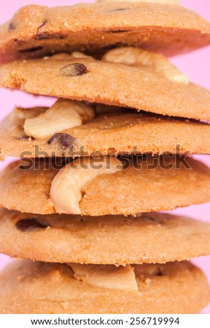 overlap of cookies cashew nut and chocolate chip on pink background - stock photo