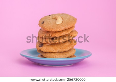 overlap of cookies cashew nut and chocolate chip put on the blue plate on pink background - stock photo