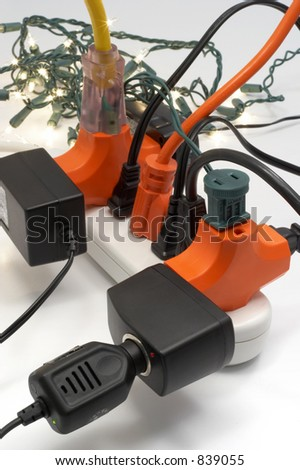 Overloaded electrical power strip with Christmas lights in background