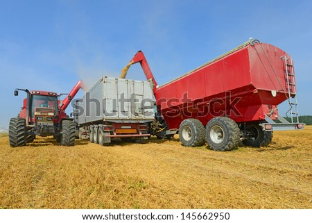 Overloading of grain bins in a car tractor. - stock photo