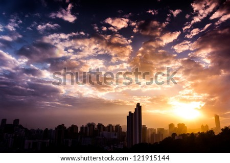 overlook of dramatic sunset and beautiful clouds pattern with blue sky over hong kong city skyline - stock photo