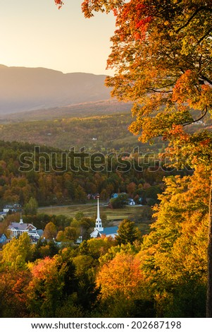 Overlooking a peaceful New England community church and village in an autumn sunset, Stowe, Vermont, USA - stock photo