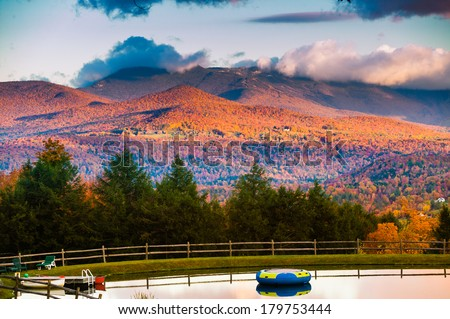 Overlooking a swimming pond with Mt. Mansfield during fall foliage in the background, Stowe, Vermont, USA - stock photo