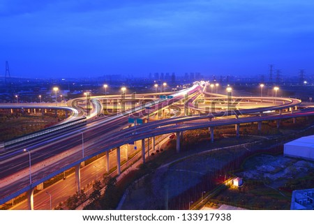 Overlooking of modern city with highway overpass in sunset night scene - stock photo