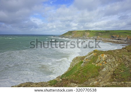 Overlooking the beach at Gunwalloe Church Cove on a very stormy day, The Lizard Peninsula, Cornwall, United Kingdom  - stock photo