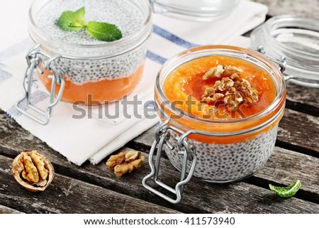 Overnight chia pudding with pumpkin puree,homemade granola,nuts and honey. Superfoods concept and healthy eating concept. Selective focus. - stock photo