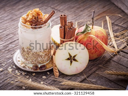 Overnight Oatmeal with yogurt, apples in the batch of ground cinnamon in a glass jar on a wooden background with apples, cinnamon and honey. The concept of healthy natural foods. selective Focus - stock photo