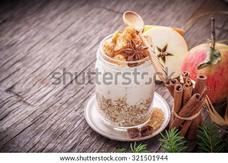 Overnight Oatmeal with yogurt, slices apples in the batch of cinnamon in glass jar on a wooden background with apples, cinnamon sticks and honey. The concept of healthy natural foods. selective Focus - stock photo
