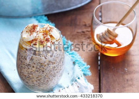 Overnight oats made with Chia seeds and fresh sliced bananas. Garnished with shaved chocolate and drizzeled honey and served outdoors. Extreme shallow depth of field.