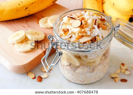 Overnight oats with bananas and nuts in snap lid glass jar on white marble - stock photo