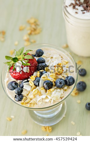 Overnight refrigerator oatmeal topped with granola, blueberries and strawberry