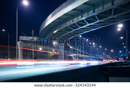 Overpass and light trails at night on the illuminated highway - stock photo