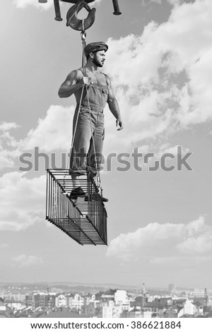 Overseeing his work. Young muscular construction worker posing on a metal crossbar monochrome shot - stock photo