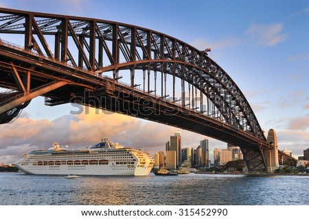 Oversized ocean cruise liner passing by under the Sydney Harbour Bridge at sunset backgrounded by city skyscrapers - stock photo