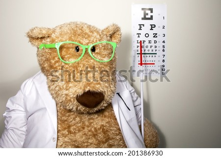Oversized teddy bear dressed as an optometrist wearing a white lab coat and glasses and pointing to a wall eye chart - stock photo