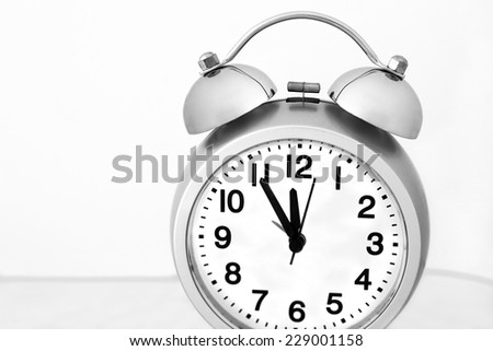 Overslept all the time - slightly tilted gray alarm clock with black and white dial showing five minutes to noon. Desaturated close up view on light gray background - stock photo