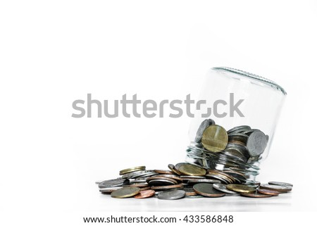 Overturn glass jar with coins spilled out, on white background - stock photo