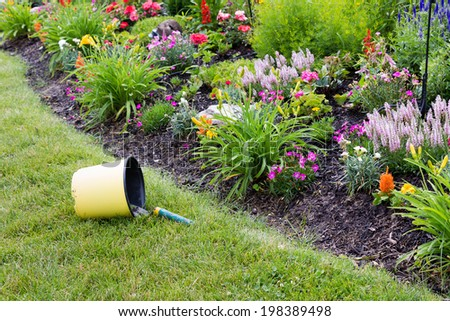 Overturned bucket containing garden tools in the grass near flowers - stock photo