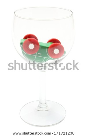 Overturned car model lying in glass of wine, car and alcohol, don't drink and drive concept. Isolated on white background - stock photo