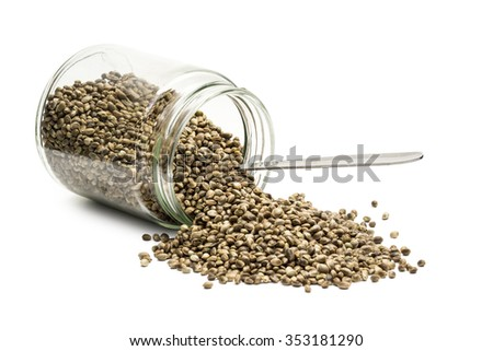 Overturned glass jar with hemp seeds and a metal spoon on white background - stock photo