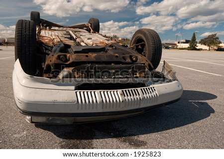 Overturned vehicle, on a deserted parkin lot - stock photo
