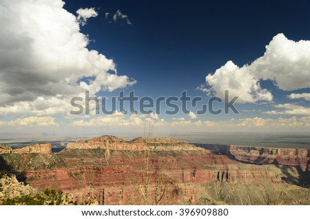 Overview Grand Canyon, colorful mountain sides, blue sky with white fluffy clouds into the distant horizon. - stock photo